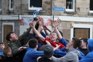 """شرکتکنندگان در مراسم سالانه بازی """"با""""، یک بازی قرون وسطایی در شهر جدبرگ اسکاتلند. هدف از بازی رساندن توپ چرمی به گل در گوشه شهر است"""
