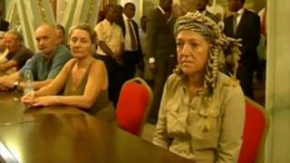 Tourists, who were held hostage, sit after they were freed in Yaounde