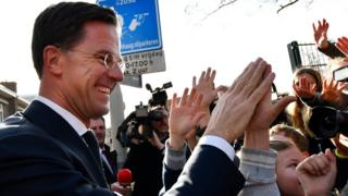 Mark Rutte high fives children after casting his vote in the Dutch general election