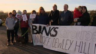 Protesters with banners at the Dewley Hill site