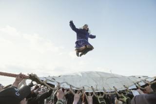"""En Nalukataq, el festival ballenero de verano, la aldea sale a celebrar que ha tenido una temporada exitosa y a agradecerle a la ballena su regalo. Aquí, los tripulantes que tuvieron éxito hacen el """"lanzamiento de manta"""". Varias personas los lanzan al aire con una manta a alturas que alcanzan los nueve metros . Dependen de la ayuda de todos para aterrizar a salvo."""