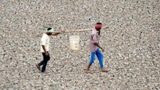 عاملان هنديان يحملان بعض الماء من بركة صغيرة على مشارف منطقة شيناي