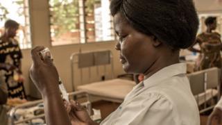 Nurse wey dey prepare injection.