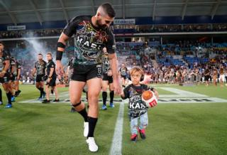 in_pictures Quaden Bayles, who lives with Achondroplasia, leads the Indigenous All Stars on to the field at a National Rugby League match. 22 February 2020