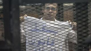 """Egyptian activist Ahmed Maher holds up a T-shirt saying """"Drop the law on demonstrations"""" at his trial on 8 December 2013"""