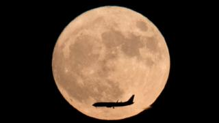 A jet plane flies across the moon seen from Beijing, China, Monday, Nov. 14, 2016