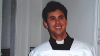 Guido sorri em foto, onde aparece de batina