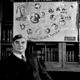 Aneurin Bevan seen with an NHS poster behind him