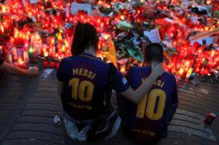 Two people sit in front of a memorial.