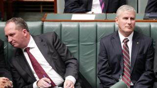 Barnaby Joyce leans away from Michael McCormack in parliament
