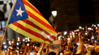 """People dey hold candles and a Catalan pro-independence """"Estelada"""" flag for demonstration in Barcelona say dem arrest of two Catalan separatist leaders on October 17, 2017."""