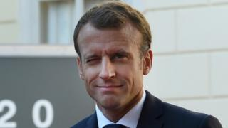 Emmanuel Macron winks at the camera in this portrait shot outside an even of European leaders