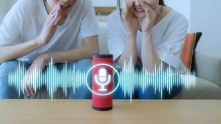hombre y mujer hablándole a un asistente de voz