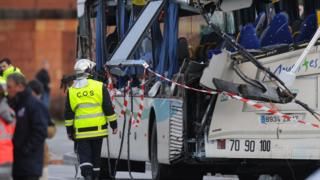 French police work near the wreckage of a school minibus after it crashed into a truck in Rochefort on February 11, 2016, killing at least six children