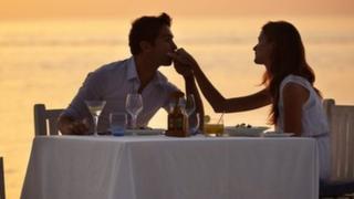 A couple enjoying a romantic dinner on the beach