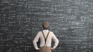 homem diante de um quadro cheio de cálculo