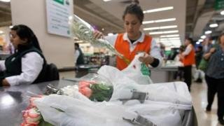 A sales assistant puts customers goods on plastic bags at a supermarket in Santiago, on July 18, 2018.