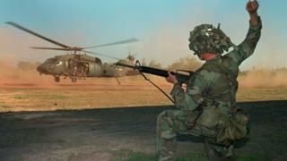 A US soldier guides a military helicopter during an operation against a military command post loyal to General Manuel Noriega on 23 December, 1989.