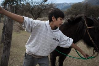 Oscar's youngest son, Pincén, playing with his pony