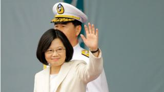 President Tsai Ing-wen waves to the crowd after her swearing in, with a man in a white military uniform standing behind her, in Taipei on 20 May 2016