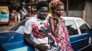 Rugby A couple leaning against a car in Bissau, Guinea-Bissau - Sunday 24 November 2019