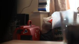 Red suitcase and plastic bags on personal possessions