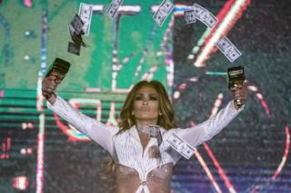 Jennifer Lopez holds a pair of money gun aloft and sprays the notes into the air.