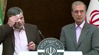 Iranian Deputy Health Minister Iraj Harirchi (L) mops his brow during a news conference on 24 February 2020