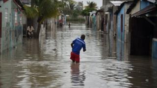A man walks in a flooded street in Port-au-Prince, Haiti
