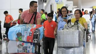 Passengers push carts with their baggage wrapped in plastic and cloth