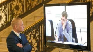 Jamie Bryson looks at TV screen showing Daithí McKay in Stormont, file pic from September 2015