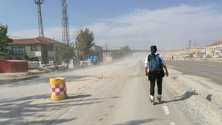 One of the students travelling by roller skate along the road