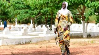 One Senegalese woman dey waka pass graves as families and friends visit di graveyard to mark di 15th anniversary of di sinking ship 'Le Joola'
