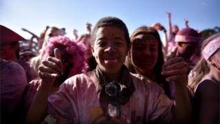 A young man sticks his tongue out as he takes part in the annual Colour run on November 12, 2016 in Cape Town, South Africa. The Colour Run is a five kilometres paint race without winners nor prizes, while runners are showered with colored powder at stations along the run.