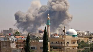 Smoke rises from the rebel-held town of Nawa, north of Deraa, Syria, during air strikes by pro-government forces (27 June 2018)
