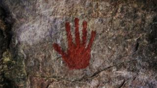 A red handprint on a cave wall.