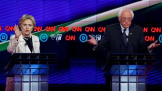 Democratic US presidential candidate Hillary Clinton (L) speaks as Senator Bernie Sanders reacts during a Democratic debate hosted by CNN and New York One at the Brooklyn Navy Yard in New York April 14, 2016.