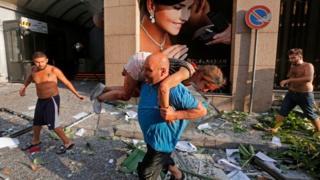 A man carries away an injured girl in Beirut