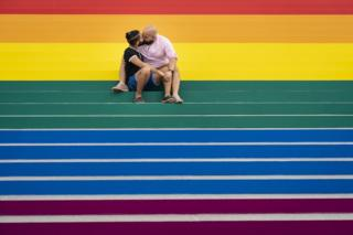 Jesus Tavarez and Juan De La O kiss on the steps that are covered in rainbow colours for Pride Month at Franklin D. Roosevelt Four Freedoms Park in New York City in June.