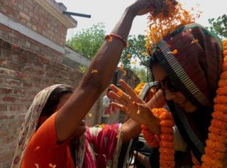 A supporter throws marigold petals at Mahua Moitra