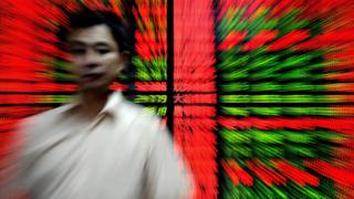 A Chinese investor walks past an electronic board showing stock index figures at a trading house in Shanghai on September 16, 2009.