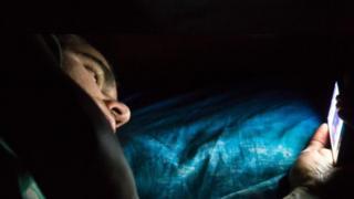 Homem ao celular na cama