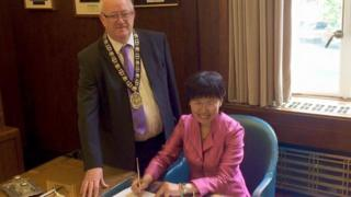 The agreement being signed in Swansea