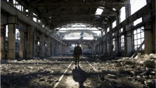 Украинский военный идет через разрушенный в результате боев цех в Авдеевке, 31 марта 2017 года