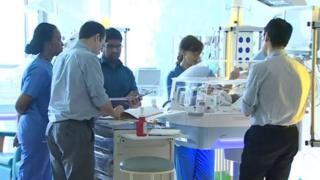 Medics gathered around an incubator
