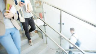 Estudantes segurando livros e celular descem escada
