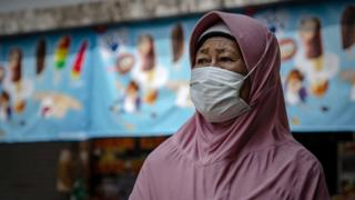 A woman wears a protective mask stands at a local bus station on March 15, 2020 in Yogyakarta, Indonesia.
