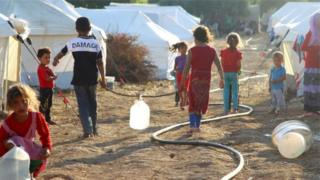 Syrian children fetching water in a refugee camp