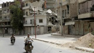Men ride motorbikes along a street in the north-western city of Ariha, after a coalition of insurgent groups seized the area in Idlib province