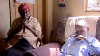 Vesta (L) and Teddy are a married couple. They sit on chairs in their home in Zimbabwe.